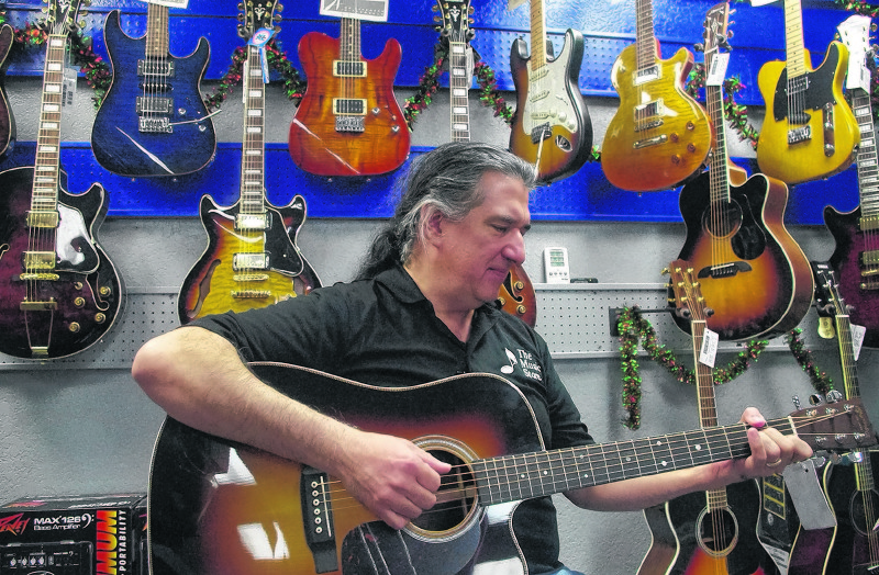 J.P. Escobedo, co-owner of The Music Store, strums one of the guitars on display at the longtime East Valley location.