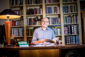 In the library of his south Tempe home, Dr. Flavio Marsiglia reviews the materials he utilizes to help individualize substance-abuse training in the communities his team visits. (Photo by Billy Hardiman/Wrangler News)