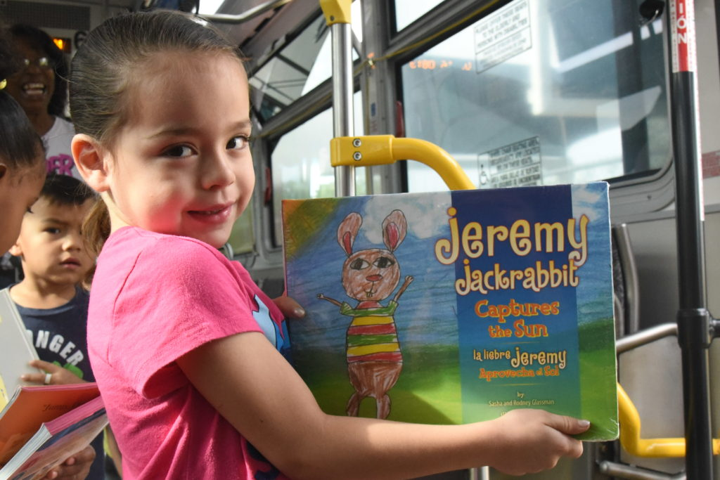 child with books donated by bus driver