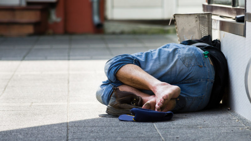 homeless man laying on side of street