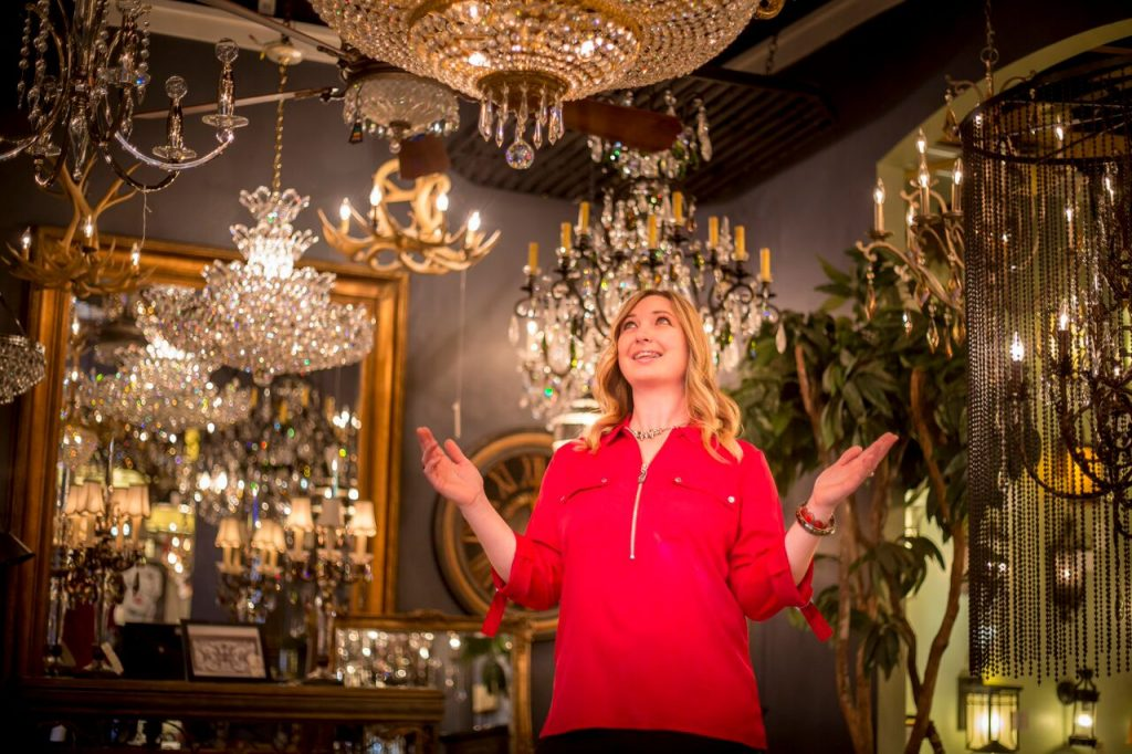 Dawn Stantus expresses wonderment at the dazzling array of lighting in the showroom that's her home away from home. Store (right) features an array of styles, choices. (Photo by Billy Hardiman/Wrangler News)